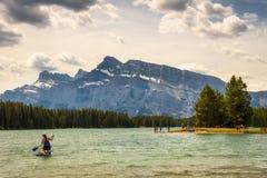 Turister tycker om en solig dag på sjön för två stålar i den Banff nationalparken Arkivfoton