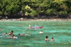 Turister tycker om med att snorkla i ett tropiskt hav på den Phi Phi islaen Arkivbilder