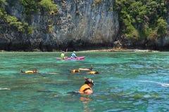 Turister tycker om med att snorkla i ett tropiskt hav på den Phi Phi islaen Arkivbild