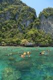 Turister tycker om med att snorkla i ett tropiskt hav på den Phi Phi islaen Royaltyfria Bilder