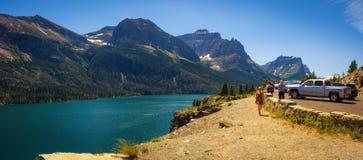 Turister tycker om sikten av helgonet Mary Lake i glaciärnationalpark Arkivfoto