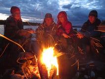 Turister värmas på en brand på natten Arkivfoto