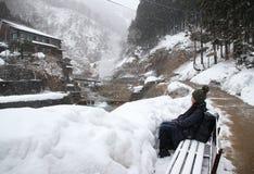 Turisti asiatici che si siedono nella neve Fotografie Stock Libere da Diritti