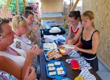 Turisti che assaggiano il formaggio del Adygei sulla presentazione del prodotto Immagini Stock Libere da Diritti