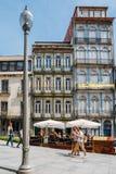 Turisti che camminano accanto alle costruzioni colourful strette con i caffè nel centro storico di Oporto - patrimonio mondiale d fotografia stock libera da diritti