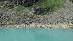 Turisti che camminano nella distanza dal lago pittoresco Kuyguk del turchese Montagne di Altai, Siberia, Russia video d archivio