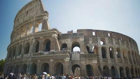 Turisti che camminano vicino al Colosseo antico dell'anfiteatro in Italia, godente del giro archivi video