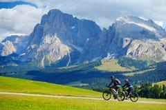 Turisti che ciclano in Seiser Alm, il prato alpino di più grande elevata altitudine in Europa, montagne rocciose di stordimento s Fotografia Stock