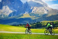 Turisti che ciclano in Seiser Alm, il prato alpino di più grande elevata altitudine in Europa, montagne rocciose di stordimento s Fotografia Stock Libera da Diritti