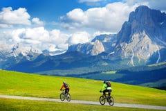 Turisti che ciclano in Seiser Alm, il prato alpino di più grande elevata altitudine in Europa, montagne rocciose di stordimento s Immagine Stock Libera da Diritti
