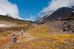 Turisti che fanno un'escursione al vulcano di Dzenzur, parco naturale di Nalychevo, Kamchatka Krai, Russia fotografia stock