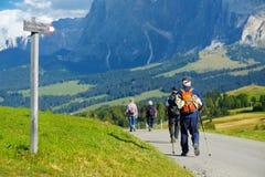 Turisti che fanno un'escursione in Seiser Alm, il prato alpino di più grande elevata altitudine in Europa, montagne rocciose di s Fotografie Stock