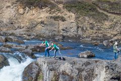 Turisti che giocano vicino alla cascata di Godafoss fotografie stock libere da diritti