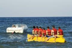 Turisti che hanno divertimento con la banana alla spiaggia Fotografie Stock