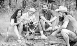 Turisti che hanno tempo dello spuntino con arrostito sopra l'alimento del fuoco Turista del gruppo degli amici che si rilassa vic fotografia stock