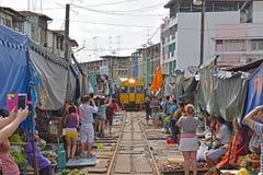 Turisti che prendono le immagini del treno ricevuto mentre i venditori hanno rimosso tutti i loro prodotti freschi Immagine Stock