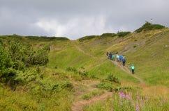 Turisti che salgono la montagna Fotografie Stock