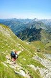 Turisti che scalano nelle alpi Immagine Stock