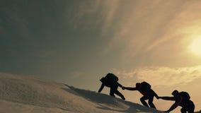 Turisti che scalano una scogliera della neve della montagna Allungamento della mano amica aiuto della gente Lavoro di squadra, co video d archivio