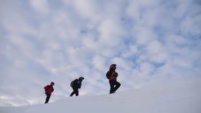 Turisti che scalano una scogliera della neve della montagna Allungamento della mano amica aiuto della gente Lavoro di squadra, co stock footage