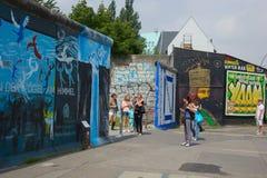 Turisti che si domandano al muro di Berlino Immagini Stock