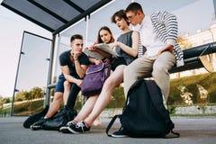 Turisti che si siedono alla fermata dell'autobus che progetta il viaggio Fotografia Stock