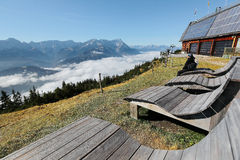 Turisti che si siedono su un banco di legno, godente della vista panoramica della montagna Zugspitze Immagine Stock