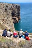 Turisti che si siedono sulle scogliere al capo St Vincent, Portogallo Fotografia Stock