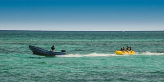 Turisti che sono rimorchiati su un giocattolo dell'acqua bahamas fotografia stock libera da diritti