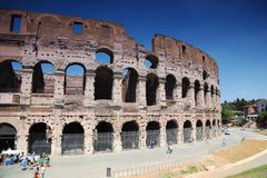 Turisti che vanno vicino alle vecchie pareti di pietra del Colosseo Fotografia Stock Libera da Diritti