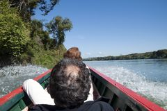 Turisti che viaggiano a monte in barca lunga fotografia stock