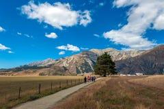 Turisti che visitano la collina in alpi del sud, il passaggio di Arthur, isola del sud del castello della Nuova Zelanda Fotografia Stock