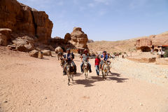 Turisti con i beduini che visitano le rovine antiche di PETRA sugli asini, Giordania Fotografia Stock Libera da Diritti