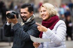 Turisti con la mappa ed i bagagli sulla via della città Fotografie Stock Libere da Diritti