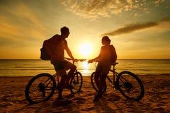 Turisti delle coppie con le biciclette che guardano tramonto La gente della siluetta Immagine Stock