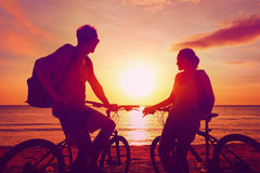 Turisti delle coppie con le biciclette che guardano tramonto La gente della siluetta Fotografia Stock Libera da Diritti