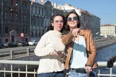 Turisti delle giovani signore nei selfies della presa di San Pietroburgo Russia su un ponte di legno nel centro urbano storico fotografie stock libere da diritti