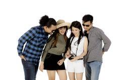 Turisti di diversità che osservano le foto su uno smartphone Fotografia Stock Libera da Diritti
