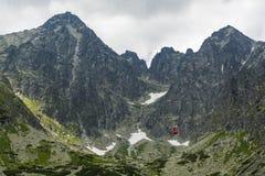 Turisti di trasporto della cabina di funivia rossa al picco di Lomnica nel Tatras in Slovacchia Immagini Stock