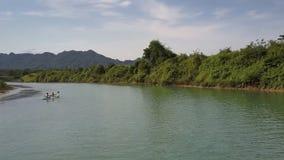 Turisti di vista aerea nella fila della barca con i remi vicino alla banca collinosa stock footage