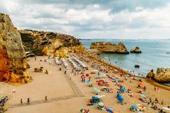 Turisti divertendosi in acqua, rilassandosi e prendendo il sole nella città di Lagos sulla spiaggia all'oceano del Portogallo Fotografia Stock Libera da Diritti
