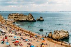 Turisti divertendosi in acqua, rilassandosi e prendendo il sole nella città di Lagos sulla spiaggia all'oceano del Portogallo Immagini Stock Libere da Diritti