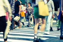 Turisti e gente di affari che attraversano la via a Immagini Stock