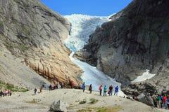 Turisti e ghiacciaio in montagne, Norvegia Immagine Stock