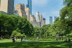 Turisti e locali al Central Park, grattacieli nel fondo Fotografie Stock