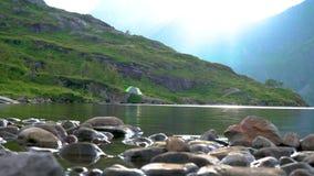 Turisti e tenda vicino al lago stock footage