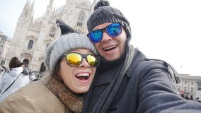 Turisti felici e piccioni che prendono un autoritratto con il telefono davanti alla cattedrale del duomo, Milano Concetto di viag stock footage