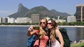 Turisti femminili di viaggiatori con zaino e sacco a pelo con lo smartphone in Rio de Janeiro con Cristo il redentore nel fondo. Fotografie Stock