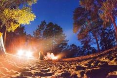 Turisti intorno al fuoco di accampamento alla notte Isola il lago Baikal di Olkhon Fotografia Stock