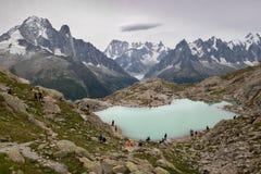 Turisti nel lago della montagna in alpi europee Immagini Stock